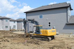 Backhoe excavating a residential basement by Superior Trenching Ltd.